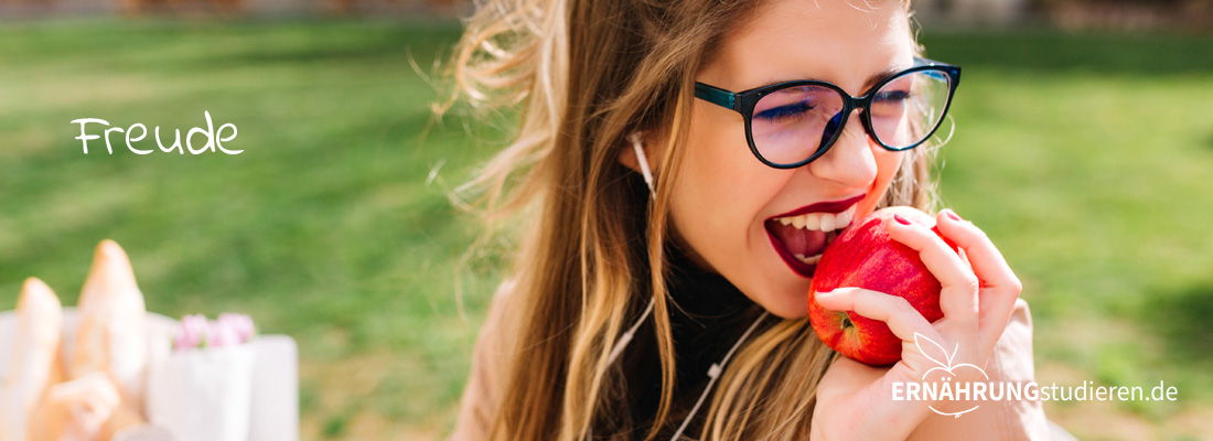 Mädchen mit Apfel freut sich.